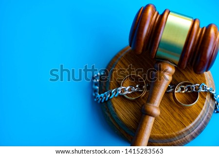Gavel separating chain between wedding rings. Divorce concept. #1415283563