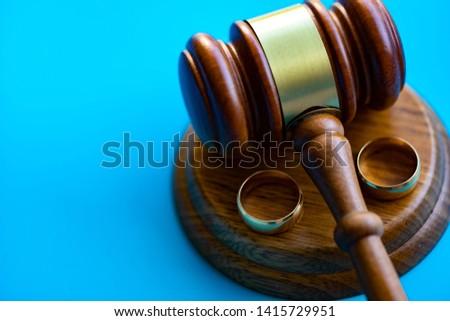 Gavel separating two wedding rings. Divorce concept. #1415729951