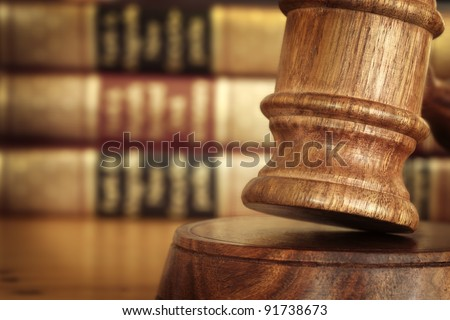 Gavel, with defocussed law books behind.