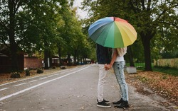 Gay couple is standing under the umbrella and holding their hands. Two men lovers in the park. Colorful umbrella like symbol of LGBT community. Equal rights