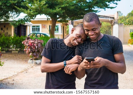 gay couple laughing together while using a phone together. two young black men walking and holding each other laughing together while viewing content on a mobile phone. Stockfoto ©