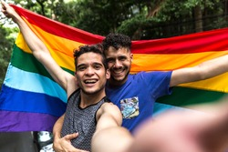 Gay Couple Taking a Selfie with Rainbow Flag in the Park