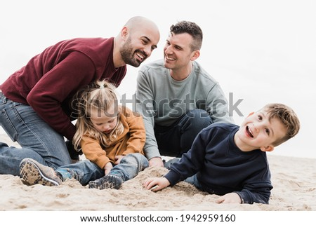 Gay fathers and sons playing on the beach in summer vacation - LGBT family love concept - Main focus on left man face Foto stock ©