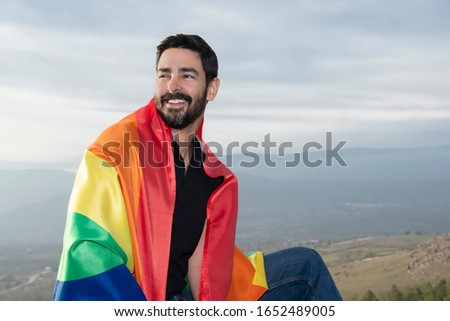 Gay laughing sitting with a gay flag looking at the horizon .concept of gay, pride, diversity