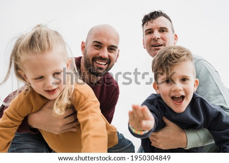 Gay male couple and little sons having fun outdoors during summer vacation - Lgbt and love family concept - Main focus on right father face Foto stock ©