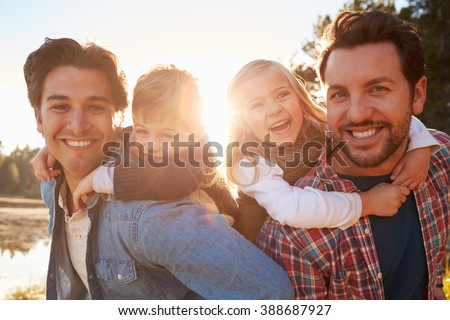 Gay Male Couple With Children Walking By Lake Stockfoto ©