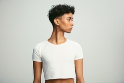 Gay man wearing crop top and earring looking away. Young androgynous man wearing earring against white background.