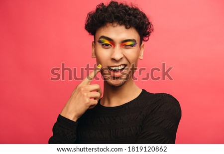 Gay man wearing multicolored shadows on the eyelids winking at camera. Happy transgender male winking an eye against red background. Stockfoto ©
