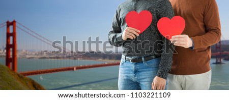 gay pride, lgbt and homosexual concept - close up of happy male couple holding red hearts over golden gate bridge in san francisco bay background #1103221109
