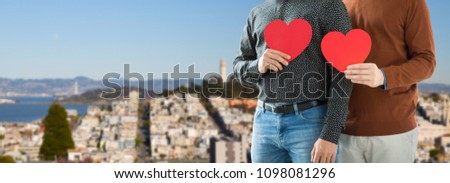 gay pride, lgbt and homosexual concept - close up of happy male couple holding red hearts over san francisco city background #1098081296