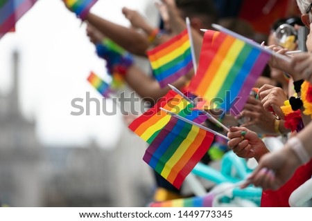 Gay pride, LGBTQ rainbow flags being waved in the air at a pride event