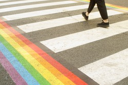 Gay Pride Month. lgbt rainbow on the pedestrian path.  Asfalt on the street, summer day. A person walking.