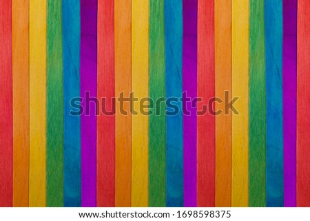 Gay rainbow LGBT flag design background. Symbol of the LGBT movement. LGBT Rights Concept. Homosexual flag texture. Wooden sticks are painted in the color of the rainbow, banner.