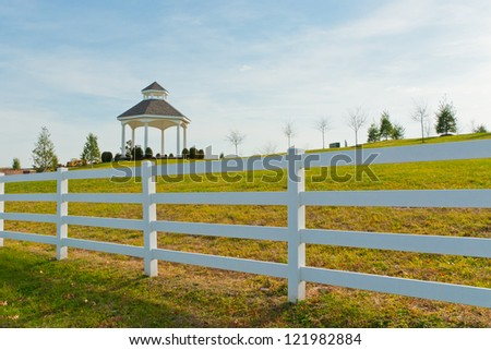 Gazebo in the new city park behind white fence at autumn