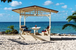 Gazebo on the Caribbean beach. Blue sky and coral sand. Inviting table and chairs very close to the sea between palm trees and shells.