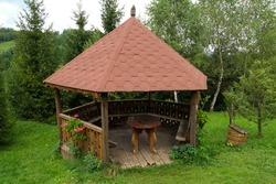 Gazebo with table in it, in garden on cotage backyard. Green grass around.