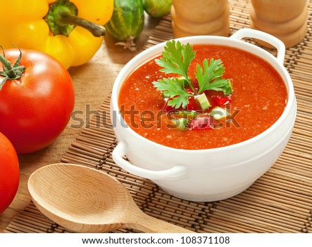 Gazpacho and ingredients on a table, vegetable soup