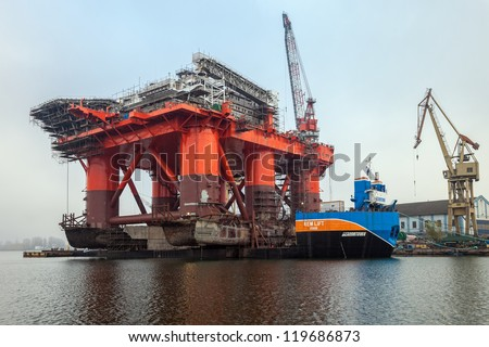 GDANSK, POLAND - NOVEMBER 23: Docking oil rig Safe Caledonia at the Gdansk Shipyard. Weighing in at 12 thousand ton colossus was pulled from the water on a barge on November 23, 2012 in Gdansk, Poland
