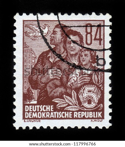 "GDR - CIRCA 1953: A stamp printed in GDR (German Democratic Republic - East Germany) shows family and pigeon , High-rise on Wiese Weber, Berlin , series ""Workers For The Five-year Plan"", circa 1953"
