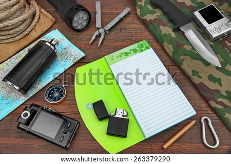 Gear laid Out For Backpacking Trip On Wood Floor Table. Items Include Rope Backpack ?amouflage Notebook  Compass,Wallet Money Binoculars Knife Machete Searchlight Flashlight Rope Pen Pencil Mug Maps #263379290