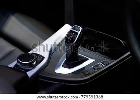 Gear lever of modern car, closeup Luxury car interior details. Car interior luxury. Interior of prestige modern car. Leather comfortable seats, multimedia. Luxurious instrument cluster. #779591368