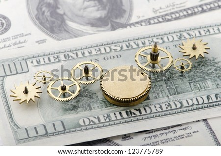 Gear of success.Gear wheels on dollar bill revealing the path to success