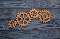Gear wheels on a wooden background. The concept of creative, logical thinking. Logic background. gears of natural wood