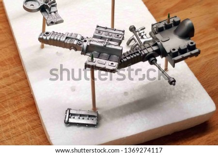 Gearbox with suspension elements, engine block, timing belt. Large-scale assembly of models. Dry painted plastic parts of cars. Hold on to the toothpicks stuck in the foam.