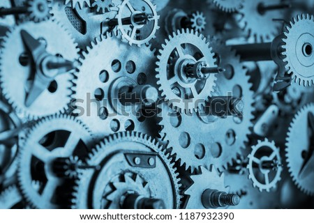 Gears and cogs macro in vintage old mechanism blue toned