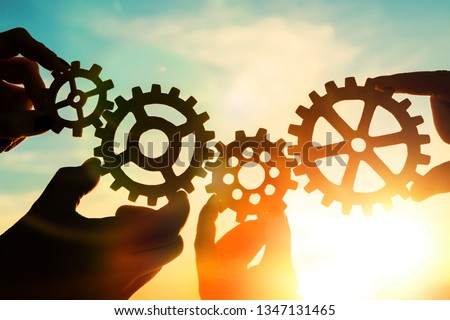 Gears in the hands of people against the sky. teamwork, interaction. #1347131465