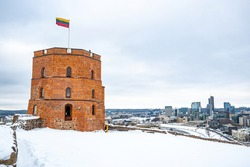 Gediminas Tower or Castle, the remaining part of the Upper Medieval Castle in Vilnius, Lithuania with Lithuanian flag in winter day with snow and skyscrapers on background