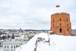 Gediminas Tower or Castle, the remaining part of the Upper Medieval Castle in Vilnius, Lithuania with Lithuanian flag in winter day with snow