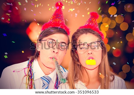 Geeky hipster wearing a party hat with blowing party horn against cookies on desk with christmas tree in background #351096533