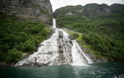 Geirangerfjord seen from the sea safari ride. Bridal veil waterfall (also known as  Brudesloret) with a height of approximately 300 meters. Norway, Scandinavia.