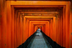 Geishas walking and sightseeing among red wooden Tori Gate at Fushimi Inari Shrine in Kyoto, Japan. Japan. Japan tourism, history building, or tradition culture and travel concept