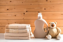 Gel for laundry washing in plastic bottle near a pile of fresh towels. Teddy bear holds detergent bottle. Composition on white wooden shelf against wooden background.
