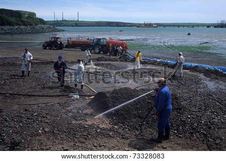 GELLISWICK BAY, MILFORD HAVEN, WALES, UK - CIRCA MAY 1996 - People clean the shoreline at Gelliswick Bay in Milford Haven after oil spill disaster of the Sea Empress circa May 1996 in Wales, UK.