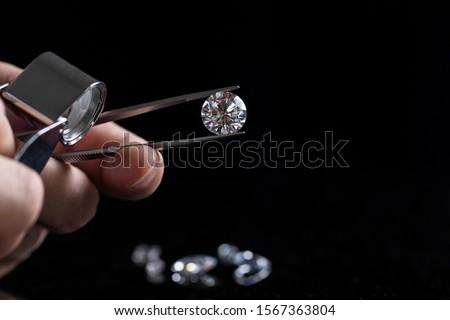 Photo of  Gem stones. Jeweller checking polished diamond. Carat size diamonds. Diamond trading and dealing. Loose diamond grading. Precious stones.