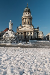 Gendarmenmarkt square in Berlin with French Cathedral, or Franzusischer Dom in German. The Schiller Monument, historic statue of Friedrich Schiller in front. Cold winter day with blue sky and snow.