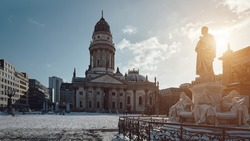 Gendarmenmarkt square in Berlin with German Cathedral, or Deutsche Dom in German. The Schiller Monument, historic statue of Friedrich Schiller in front. Cold winter day with blue sky and snow.