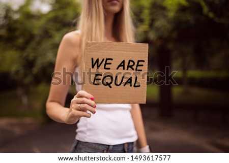 Gender equality concept as woman hands holding a paper sheet with inscription We are equal over a city street background. Woman protesting outdoor. Metaphor of social issue.