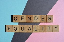 Gender Equality, words in wooden alphabet letters isolated on pink, blue and grey background