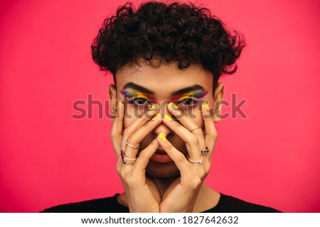 Gender fluid male wearing rainbow colored eye shadow and smiley face on fingernail. Transgender male with funky makeup on red background.