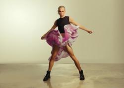 Gender fluid young man in crop top and skirt dancing in studio. Gay man dancing in flowy skirt