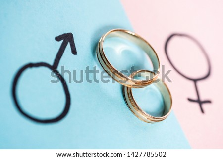 Gender symbols Venus and Mars indicate man and woman on blue and pink paper with two wedding rings. Heterosexual marriage. #1427785502
