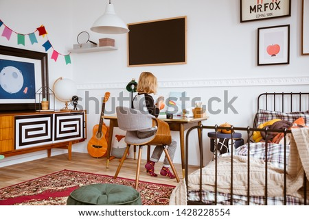 Genderless bedroom with kid painting at the retro desk in tenement house