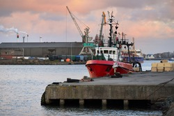 General cargo ship and fishing boat anchored in a trading port. Cranes in the background. Liepaja, Latvia, Baltic sea. Freight transportation, logistics, global communications, industry, economy