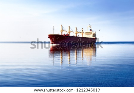 General cargo ship sailing in still water with its reflection near the port of Riga. Baltic sea