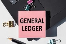 GENERAL LEDGER note is written on a paper sticker on a laptop keyboard.