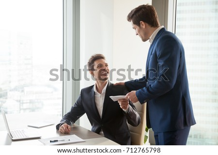General manager presenting an envelope with premium or bonus cash to male company official. Boss congratulating happy employee with career promotion, thanking for good job and giving financial reward